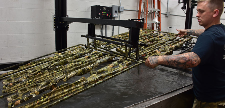 picture of a splashed hydrographic expert hydro dipping some camouflage weapons, camo dipping, picture of a splashed hydrographics expert water transfer printing camouflage onto weapons