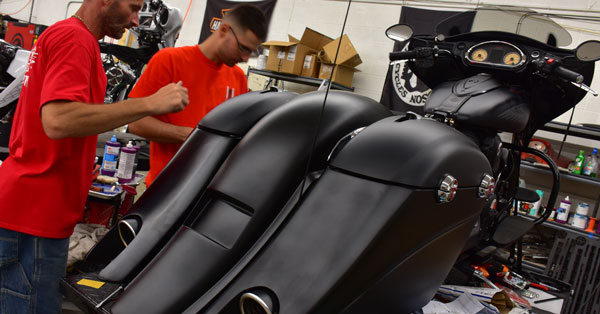 picture of a hydro dipped customization for an indian motorcycle that is matte black, picture of splashed hydrographics professionals working on a indian motorcycle customization, water transfer printing