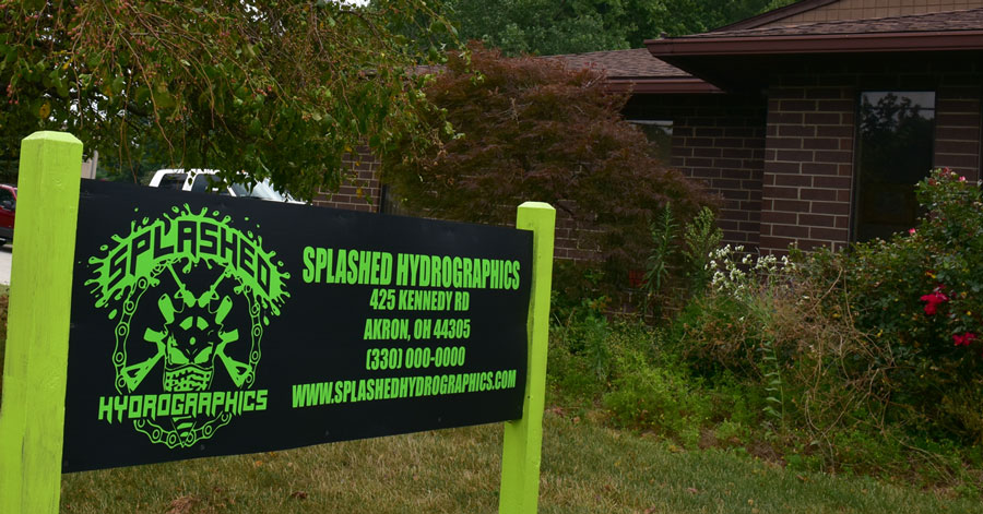 splashed hydrographics front sign with building in the background, hydro dipping business in akron with the splashed hydrographics sign in the front and building in the background,