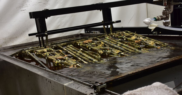 splashed hydrographics gun rack going into the water transfer printing stage, picture of a weapon rack being hydro dipped with a camouflage print pattern, hydro dipping, water transfer printing