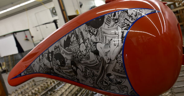 picture of a motorcycle gas tank after being hydro dipped with a black and white women graphic, splashed hydrographics motorcycle tank after being water transfer printed on