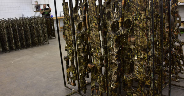 picture of a weapons rack with camouflage weapons on it after being hydro dipped, water transfer printing on weapons, splashed hydrographics water transfer printing on a rack of weapons