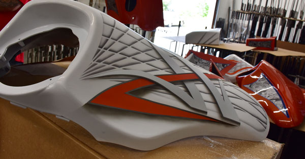 picture of a white and orange motorcycle part that was water transfer printed on, splashed hydrographics water transfer printing job on some motor cycle parts with weapon racks in the background, hydro dipping motorcycle parts white and orange