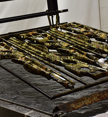 camo dipping, picture of a rack of camouflage weapons on a rack being camo dipped into a tank of water