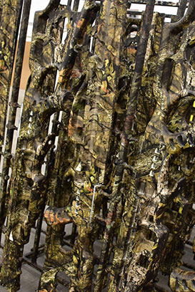 camo dipping, picture of rack of weapons after being camo dipped with a camouflage pattern
