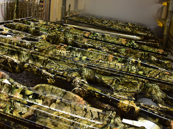 camo dipping, picture of camouflage weapons going through the spray wash station after being camo dipped