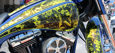 picture of a hydro dipped motorcycle that has a yellow skull and women design water transfer printed on it