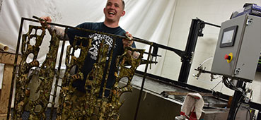 picture of a splashed hydrographics professional holding up some camouflage weapons after they were hydro dipped with a camouflage design