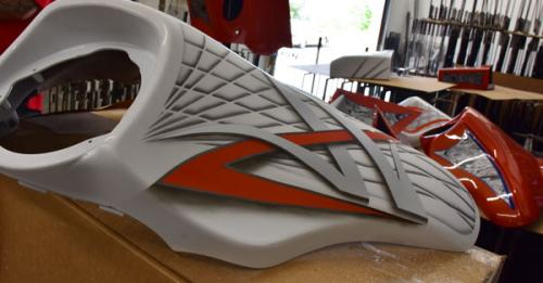 picture of a white and orange motorcycle part that was water transfer printed on, splashed hydrographics water transfer printing job on some motor cycle parts with weapon racks in the background, hydro dipping motorcycle parts white and orange, hydrographics photo gallery
